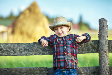 Close up portrait of little boy in hat with straw in mouth leaned on wooden fence