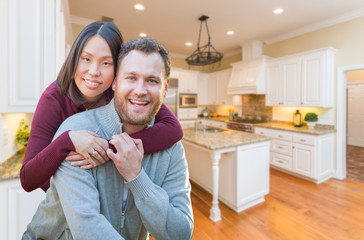 Mixed Race Caucasian and Chinese Couple Inside Beautiful Custom Kitchen.