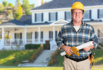 Contractor With Plans and Hard Hat In Front of Beautiful Custom House.