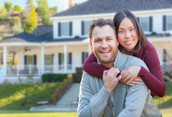 Mixed Race Caucasian and Chinese Couple In Front Yard of Beautiful Custom House.