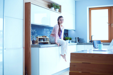 Young woman sitting on table in the kitchen.