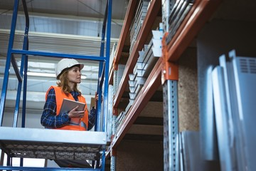 Female worker maintaining record on digital tablet in the factory