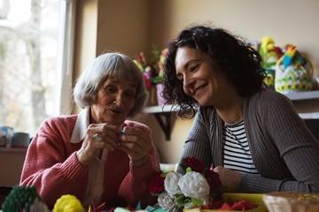 Senior woman interacting with caretaker at nursing home