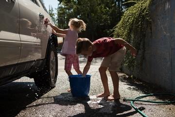 Siblings washing a car at outside garage