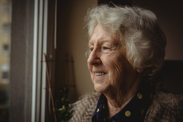 Smiling senior woman looking out of the window