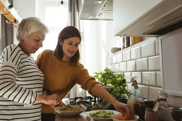 Senior woman and daughter cooking together in the kitchen