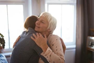 Senior woman embracing her daughter in living room