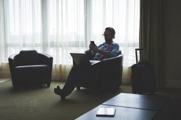 Businessman using mobile phone while sitting on arm chair