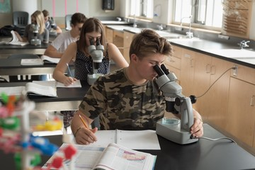 College students experimenting on microscope in laboratory