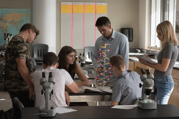 Teacher assisting students in experiment on molecule