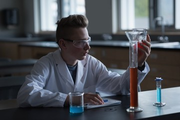 Teenage boy experimenting chemical solution