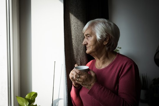 Senior woman having cup of tea while looking out of window