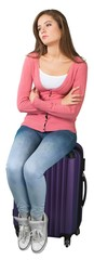Young cute woman sitting on suitcase on white background