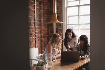 Female executives discussing over laptop with each other