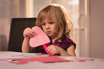 Girl preparing heart shape decoration with craft paper