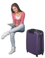 Portrait of a Woman Sitting with Luggage and Using Tablet
