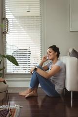 Happy woman talking on mobile phone near sofa