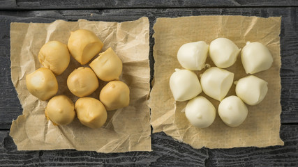 Freshly prepared smoked and regular mozzarella cheese in paper on a black wooden table.
