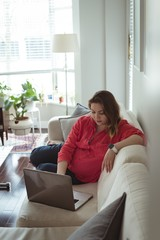Young pregnant woman sitting on sofa using her laptop