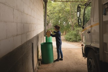 Woman pouring water into storage barrel