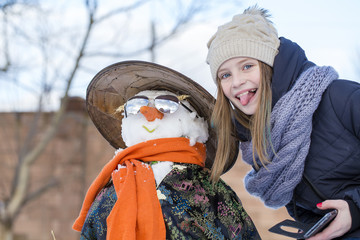 Happy young girl is taking pictures of selfie with a snowman. Ukraine