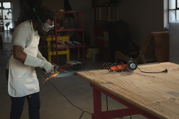 Carpenter cutting metal with electric saw