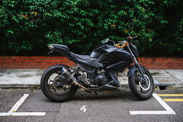 Black motorcycle. Sport motorcycle in the Parking space. Marking of Parking on the pavement.