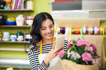 Asian female florist calling on smartphone and making notes at flower shop counter
