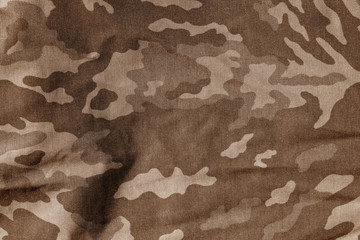 Military uniform pattern with blur effect in brown color.