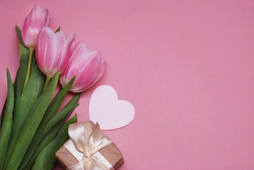Pink Tulips on the Pink Background. Flat Lay, Top view. Valentines Background. Gift Box and Paper Heart. Mother's Day or Valentine'sDay or Women's Day.