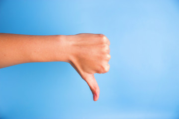Closeup of woman's hand gesturing thumbs down