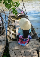 Woman in traditional dress on wooden boat
