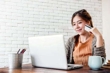 Young Woman Shopping with Credit Card and Laptop at Home, Happy Female Buying Products via Online