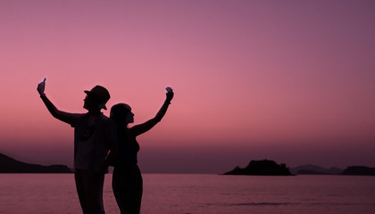 Love Concept, Silhouette of Couple having Romantic Moment and using Smart Phone at Twilight Sea, Valentines Day Background