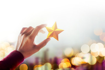 Human Resource Management or Talent Concept, Hand holding and Raise up a Golden Star, Blured Bokeh Light as background