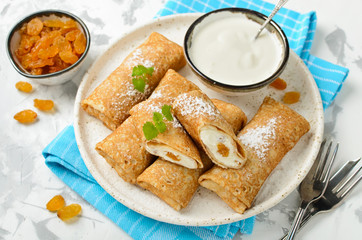 Pancakes stuffed with cottage cheese and raisins
