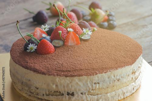 Round tiramisu cake on wood table sprinkle with cacao powder and