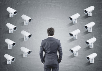 Many CCTV cameras on one wall, rear view of a man