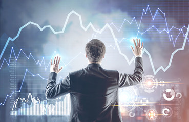 Businessman with hands in the air, graphs