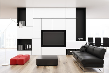 White living room with a black sofa, red