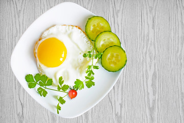Scrambled eggs with cucumbers and tomatoes on plate on wooden table, top view