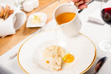 Broth with dumplings and an egg yolk being poured from a jug
