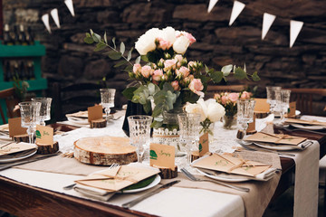 Little dinner table served in rustic style and decorated with pink flowers stands outside
