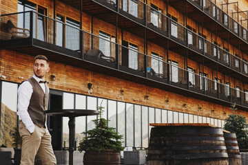Thoughtful man walks alone before a wooden mountain hotel