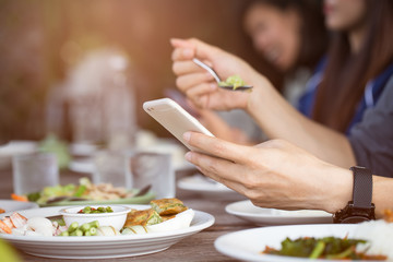 close up of Man hand using or looking at his smartphone and having lunch in the restaurant with friends.