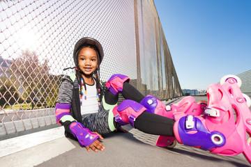 Girl in roller skates sitting on the floor of park