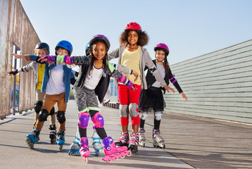 Happy little roller skaters having fun outdoors