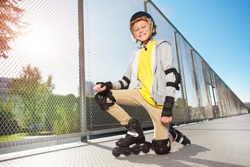 Happy roller skater posing on floor at skate park