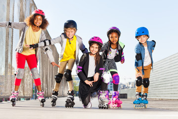 Happy kids rollerblading outdoors at sunny day