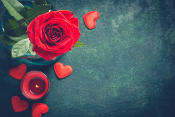 Valentines day greeting card concept. Red rose and candle on  blue background